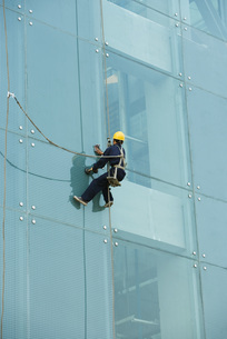 Window washer on side of office buildingの写真素材 [FYI04319568]