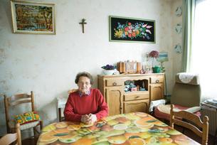 Senior woman sitting in home interiorの写真素材 [FYI04319683]
