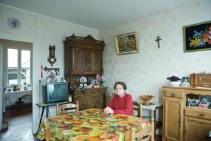 Senior woman sitting in home interiorの写真素材 [FYI04319685]