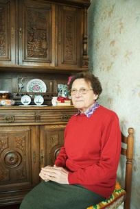 Senior woman sitting in home interiorの写真素材 [FYI04319695]