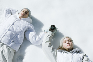 Girls lying on snow with eyes closedの写真素材 [FYI04319860]