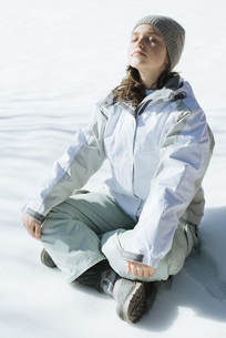 Girl sitting indian style on snowの写真素材 [FYI04319861]