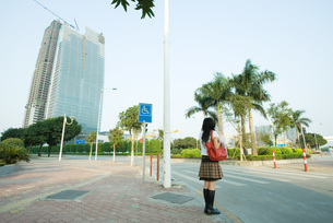 Young woman waiting to cross streetの写真素材 [FYI04319906]