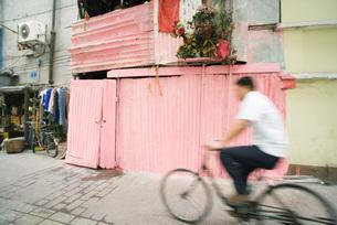 man riding bicycle through streetの写真素材 [FYI04319909]