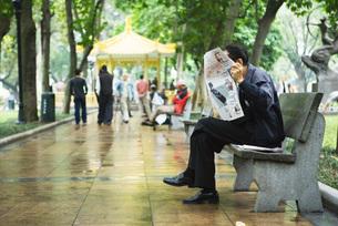 man reading newspaper on benchの写真素材 [FYI04319917]