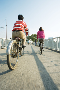 Cyclists crossing bridge, rear viewの写真素材 [FYI04319918]