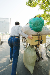 Man pushing bike laden with packagesの写真素材 [FYI04319919]