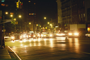 Cars pulling out from stoplight at nightの写真素材 [FYI04320022]