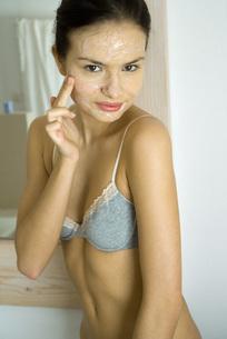 Woman in underwear applying facial maskの写真素材 [FYI04320033]