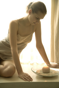 Girl in slip sitting in window at candleの写真素材 [FYI04320038]