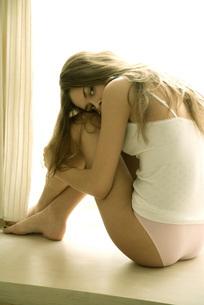 Woman in underwear hugging kneesの写真素材 [FYI04320044]