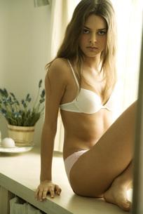 Woman sitting in underwear, staringの写真素材 [FYI04320045]