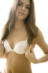 Woman in bra holding ends of hairの写真素材 [FYI04320047]