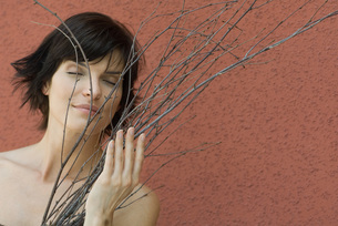 Woman holding dry branches, eyes closedの写真素材 [FYI04320055]