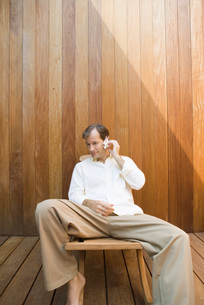 Man sitting and listening to seashellの写真素材 [FYI04320092]