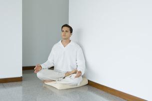 Man sitting in lotus position on cushionの写真素材 [FYI04320094]