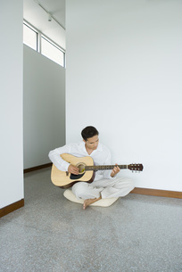 Man sitting and playing acoustic guitarの写真素材 [FYI04320095]