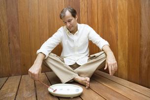 Man sitting and raking rock gardenの写真素材 [FYI04320096]