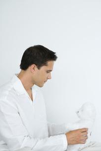 Man dressed in white holding teddy bearの写真素材 [FYI04320099]