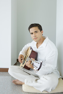 Man sitting and playing acoustic guitarの写真素材 [FYI04320100]
