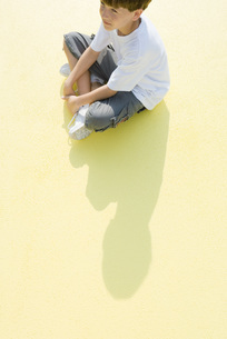Boy sitting indian style on the groundの写真素材 [FYI04320112]