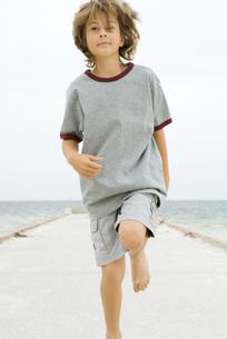 Boy running on pier, looking awayの写真素材 [FYI04320122]