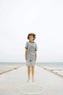 Boy jumping over plastic hoopの写真素材 [FYI04320125]