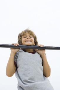 Boy doing pull-up, chin resting on barの写真素材 [FYI04320134]