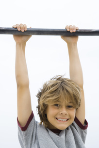 Boy hanging from metal bar at cameraの写真素材 [FYI04320136]