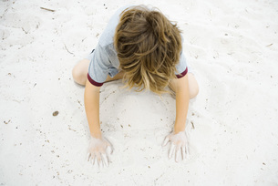 Boy crouching in sand, playingの写真素材 [FYI04320140]