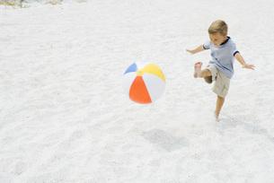 boy kicking beach ball at the beachの写真素材 [FYI04320153]