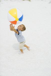 boy catching beach ball, arms raisedの写真素材 [FYI04320155]
