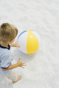 Boy standing and reaching for beach ballの写真素材 [FYI04320156]