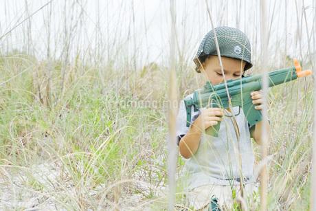 boy playing with toy gun, wearing helmetの写真素材 [FYI04320159]