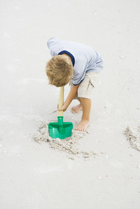Young boy digging in sand with shovelの写真素材 [FYI04320160]