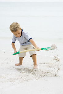 Boy digging in sand with shovelの写真素材 [FYI04320163]