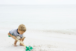 Boy digging in sand with shovelの写真素材 [FYI04320164]