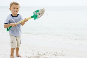 boy holding up shovel and throwing sandの写真素材 [FYI04320165]