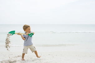 Boy holding up shovel and spilling sandの写真素材 [FYI04320166]