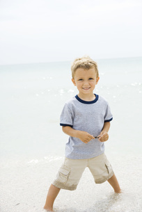 Boy standing ankle deep in waterの写真素材 [FYI04320171]