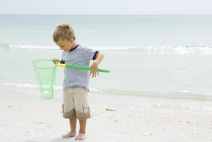 Boy holding ball in netの写真素材 [FYI04320178]