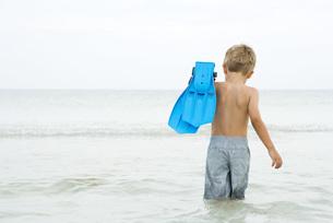 boy wading in ocean, carrying flippersの写真素材 [FYI04320187]