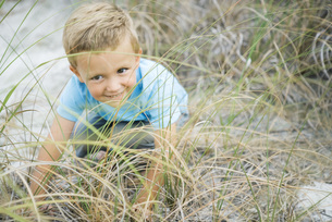 boy crouching in tall grass, smilingの写真素材 [FYI04320192]
