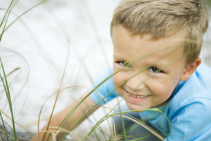 boy crouching in tall grass at cameraの写真素材 [FYI04320193]