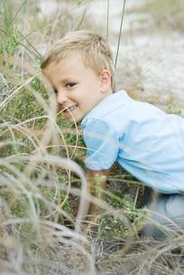 Boy crouching in tall grassの写真素材 [FYI04320195]