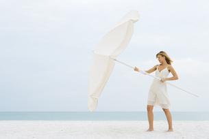 Woman opening large beach umbrellaの写真素材 [FYI04320203]