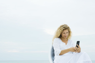 Woman sitting and looking at cell phoneの写真素材 [FYI04320207]