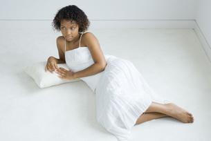 Woman lying on cushion on the groundの写真素材 [FYI04320210]
