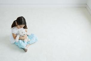 Girl holding teddy bear on lapの写真素材 [FYI04320212]
