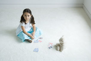 Girl playing card game with teddy bearの写真素材 [FYI04320214]